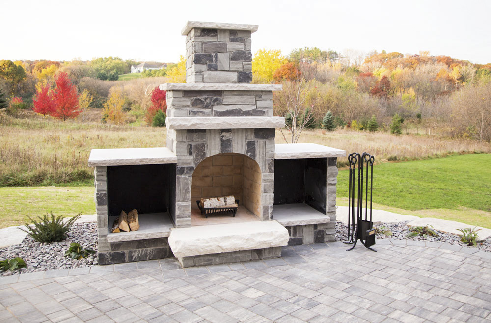 A natural stone fireplace is the focal point of this paver patio.